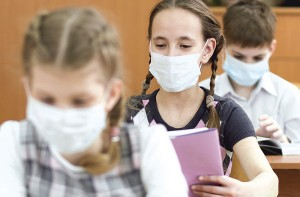 Schoolkids with protective mask on faces against coronavirus or flu in classroom
